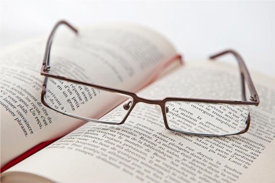Wissensdurstig in die Rente - Buch, worauf eine Brille liegt